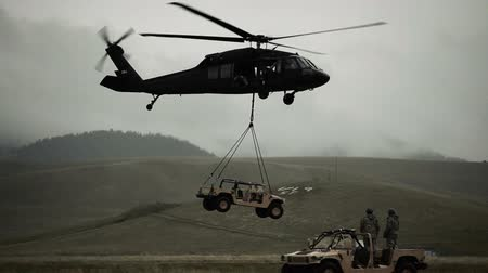 piloto : Shot of Humvee being set down by Black Hawk helicopter in field with another Humvee in foreground ready to be lifted. Green Beret United States Army Special Forces.