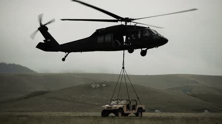 piloto : Shot of Black Hawk helicopter hauling off Humvee from field. Green Beret United States Army Special Forces.