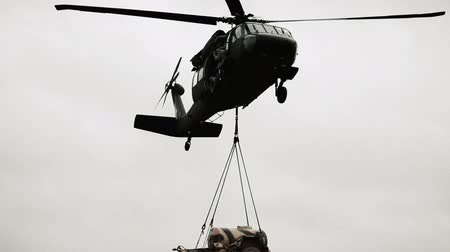 sas : Black Hawk helicopter flying away carrying a fuel tank trailer. Green Beret United States Army Special Forces.