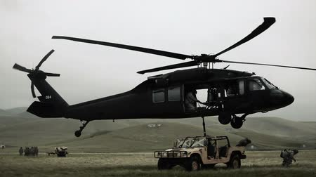 war : Shot of Black Hawk helicopter attaching and hauling off Humvee from field. Green Beret United States Army Special Forces. Stock Footage