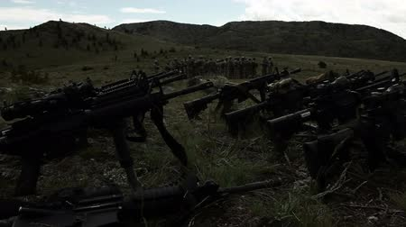 стрельба : Panning shot of assault rifles in foreground with group of soldiers in background; soldier also seen packing gear. Green Beret United States Army Special Forces. Стоковые видеозаписи