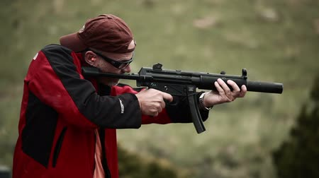 стрельба : Stationary shot of a man in sunglasses and a backwards baseball cap shooting an MP5. A lot of smoke comes off the end of the gun and people can be heard in the background of the shot praising the mans aim. From Green Beret United States Special Forces tr