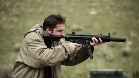 shooting range : Stationary shot of a man in a tan jacket shooting an MP5. A lot of smoke comes off the end of the gun and people can be heard in the background of the shot praising the mans aim. From Green Beret United States Special Forces training
