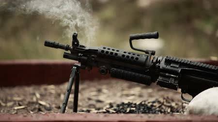 стрельба : Stationary shot of a machine gun with copious amounts of smoke blowing off the end. Green Beret United States Special Forces
