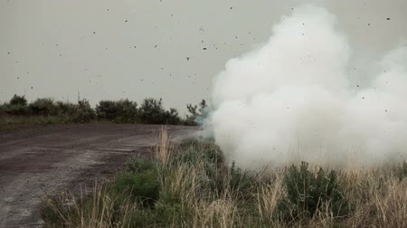 kazık : A training explosive on the side of a dirt road near a post. It gives off smoke and then blows up. From a training for Green Beret United States Army Special Forces.