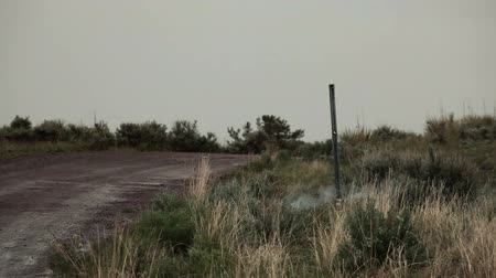 bomba : A training explosive on the side of a dirt road near a post. It gives off smoke and then blows up. From a training for Green Beret United States Army Special Forces.