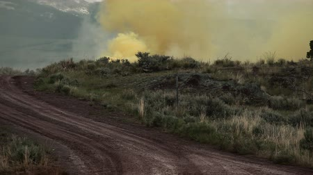взрывной : Yellow smoke signal on the side of a dirt road. There are also training explosives giving off smoke and exploding. Part of a training for Green Beret United States Army Special Forces. Стоковые видеозаписи