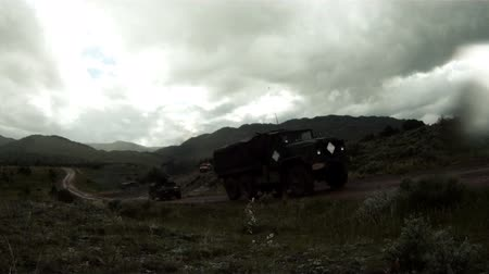 erkeklere özel : Sped-up footage of Humvees and a covered truck forming a convoy driving along a dirt road as part of a training for Green Beret United States Army Special Forces. It is raining and training explosives are exploding and giving off smoke.