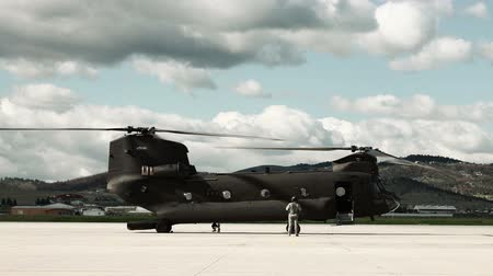 ranvej : Slightly sped-up footage of a CH-47 Chinook Helicopter at an airfield. The helicopter is stationary but it is running and the rotors are spinning. There is a beautiful, cloudy sky above. From a training for Green Beret United States Army Special Forces.