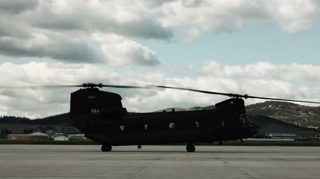 motor vehicle : CH-47 Chinook Helicopter starting up. The tandem rotors spin faster and faster. From a training for Green Beret United States Army Special Forces. Stock Footage