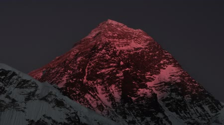 Time-lapse of Mount Everest at sunset. The sunlight on the peak and west face turns red and then fades to black. Cropped.