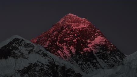 Time-lapse of Mount Everest at sunset. The sunlight on the peak and west face turns red and then fades to black. Panning shot.