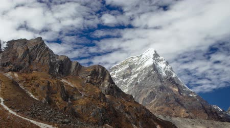Time-lapse of clouds passing over rocky Himalayan peaks. Panning shot.