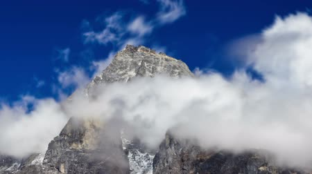 Time-lapse of clouds swirling around a Himalayan peak. Panning shot.