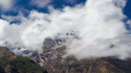 Time-lapse of clouds moving around Himalayan mountains. Panning shot.