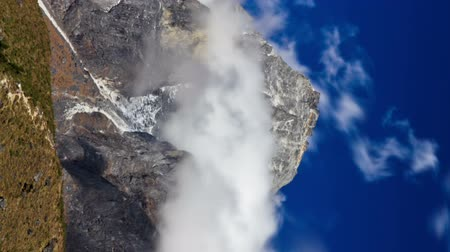 Time-lapse of clouds swirling around a Himalayan peak. Vertical shot.