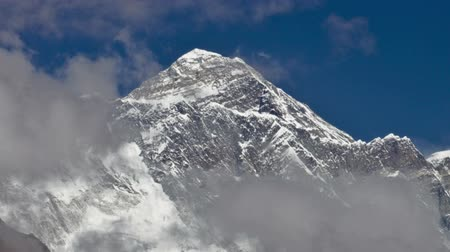 Time-lapse of clouds swirling around the summit of Mount Everest. The peak on the right is perhaps Lhotse. Panning shot. Стоковые видеозаписи