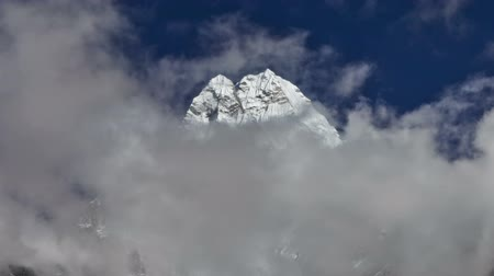 Time-lapse of clouds passing in front of a Himalayan peak. Panning shot. Стоковые видеозаписи