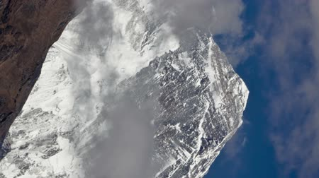 Time-lapse of clouds swirling around the summit of Mount Everest. The peak on the right is perhaps Lhotse. Vertical shot.