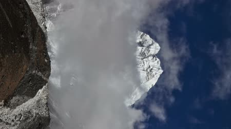 Time-lapse of clouds passing in front of a Himalayan peak. Vertical shot.