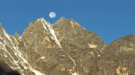 Time-lapse of the moon going behind Himalayan peaks in the morning. Shadows advance as the sun rises. Cropped. Стоковые видеозаписи