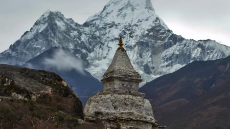 Time-lapse of a buddhist stupa in the Himalaya with Ama Dablam peak in the background. There are eyes painted on the rocky stupa. Clouds swirl around and above the mountains. Cropped.
