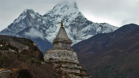 Time-lapse of a buddhist stupa in the Himalaya with Ama Dablam peak in the background. There are eyes painted on the rocky stupa. Clouds swirl around and above the mountains. Panning shot. Dostupné videozáznamy