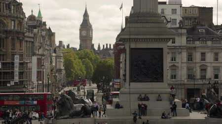 visitantes : Big Ben shot at Trafalgar Square with red double decker and tour buses driving by and a flag in the waving in the distance in London, England. Filmed on October 9, 2011.