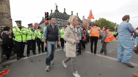 protestor : People protesting in London near Westminster because the government slashed some of their healthcare coverage. Policeman keep things in control in London, England. Filmed on October 9, 2011. Stock Footage