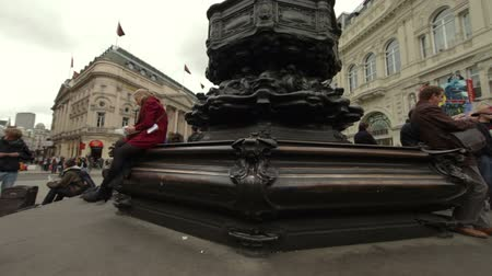 bronz : Man and a woman sitting on opposite ends of the famous Eros statue with birds walking around their feet while at Piccadilly Circus in London, England on October 7, 2011.