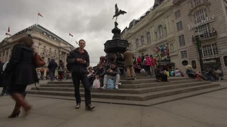 bronz : Shot of people sitting and walking around the steps of the Eros statue in London, England on October 7, 2011.