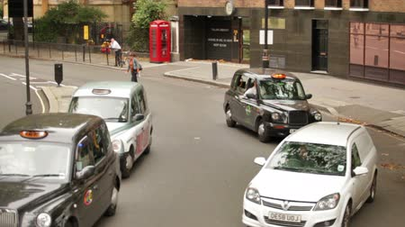 motor vehicle : Stationary view of unidentified people in cars and an unidentified biker drive on a road in London, England. Filmed on October 11, 2011. Stock Footage