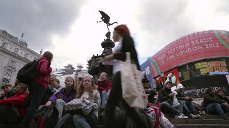 bronz : A crowd of people sit on the steps of the famous Eros statue at Piccadilly Circus in London, England. Filmed on October 7, 2011. Stok Video