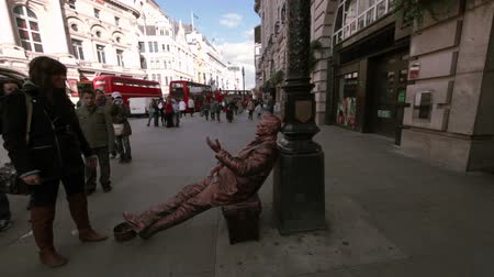 dvojitý : A lady putting money into the hat of a street performer sitting on a bench imitating a statue with red double decker buses at piccadilly in London, England
