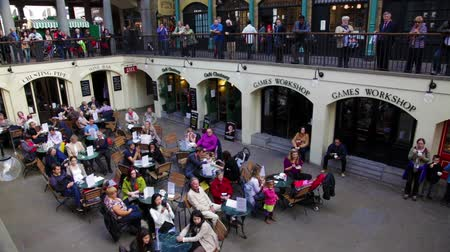 covent : People sitting at tables at Covent Garden in London, England.
