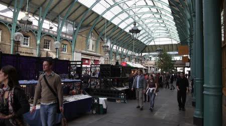 covent : A shot of the shops at Apple Market with people walking by in London, England.