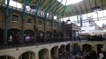 covent : People sitting at tables and walking around at Covent Garden in London, England.