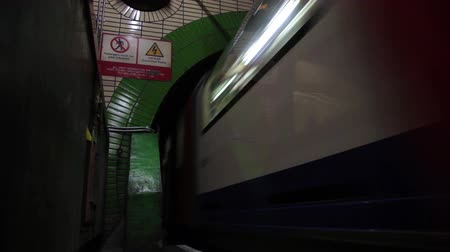 londyn : The underground tube speeding through and out of the tunnel, slowing down into a stop in an underground station in London, England. Filmed on October 6, 2011.