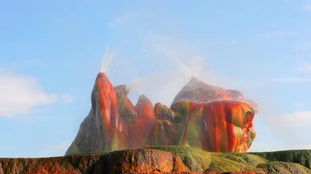fennsík : A close up shot of mist flying off some some smooth, strange looking rocks on top of a small plateau. The rocks are red, green, and orange. Filmed at Fly Geyser in Nevada. Stock mozgókép