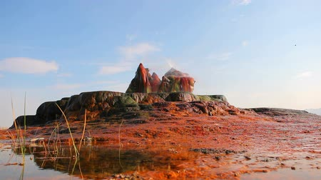 zajímavý : Shot from the ground looking out at the colorful and interesting rock formations and mineral deposits of Fly Geyser, Nevada. Hot water is spouting out of smooth, strange looking rocks on top of a small plateau. The rocks are red, orange, and green.