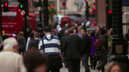 dvojitý : A stationary shot of people and traffic on a street in London. Some buses are passing by on the road and a lady is running on the sidewalk. Filmed on October 7, 2011. Dostupné videozáznamy