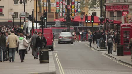 dvojitý : A stationary shot of people and street traffic in London. People walk on the pavement and cross the street. Buses, cars and vans drive by. There are traffic lights too. Filmed on October 7, 2011. Dostupné videozáznamy