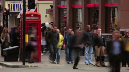 dvojitý : A stationary shot of pedestrians waiting to cross the street in London. Some cars and buses, including London sightseeing tour bus, drive by and a building can also be seen. Filmed on October 7, 2011.