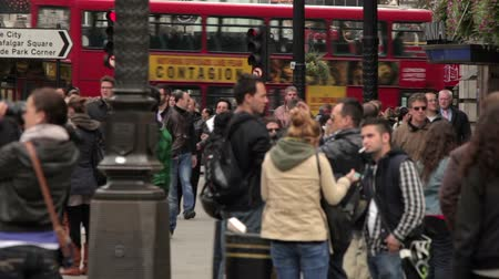dvojitý : A stationary shot of people and passing buses on Piccadilly Circus in London. A city tour bus and a regular red double-decker pass by. There is a sign, showing the direction to Trafalgar Square. Filmed on October 7, 2011.