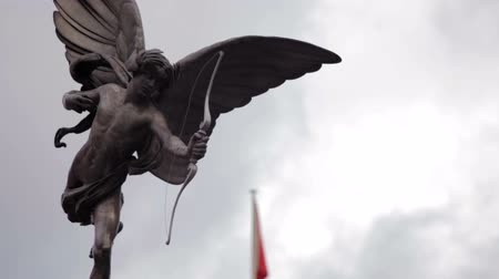 божество : A stationary close-up shot of Eros statue on Piccadilly Circus in London. A flag is waving in the background, which is defocused. Filmed on October 7, 2011.