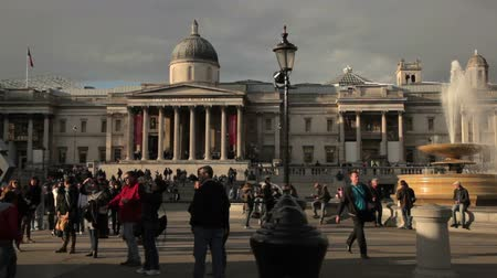 kolumna : A stationary panoramich shot of National Gallery on Trafalgar Square in London. People are either standing or walking about on the square and on the right there is a fountain. Filmed on October 7, 2011.