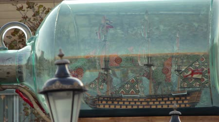 lampy : A panning shot - from right to left - of a ship inside a bottle, a replica of admiral Nelsons ship victory made by Yinka Shonibare. A building is in the background and a lamp post in the foreground. Filmed in front of National Gallery in London on Octobe
