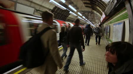 exiting : People walking in the underground station as the tube speeds away, exiting the station in London, England. Filmed on October 6, 2011. Stock Footage