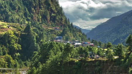 Time-lapse of a Himalayan valley with a river and a small village. There is a hanging bridge over the river and billowing clouds in the sky. Panning shot.
