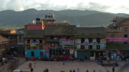 Time-lapse of dusk at Taumadhi square in Bhaktapur, Nepal. Bhairavnath temple is seen, as well as pedestrians walking through the plaza. Cropped.